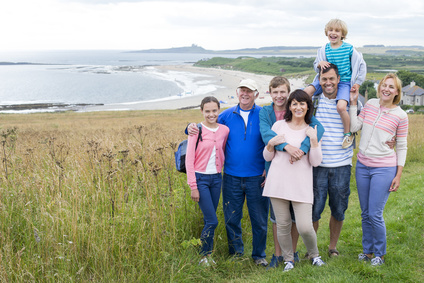 A family are standing on the sand dunes, they are all smiling and looking at the camera.